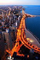 Traffic illuminates Lake Shore Drive in Chicago at dusk.