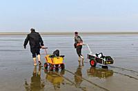 Wanderer im Watt ziehen Bollerwagen mit Strandgepäck über die Wattfläche, Nationalpark Schleswig-Holsteinisches Wattenmeer, Westerhever, Schleswig-Hol...