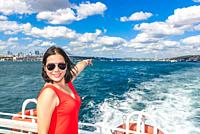 Beautiful Chinese woman shows First Bridge while cruising with ferry in Istanbul,Turkey.