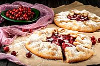 Two of gooseberry galette. Berries of gooseberry on a wooden table and in plate, decorative mesh. The cut out sector of the pie.