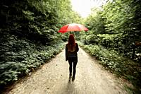 Girl walking through the forest with red umbrella, Navarra. Spain.