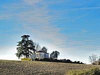 empty farm field and Saint-Macaire church, Lot-et-Garonne Department, New Aquitaine, France.