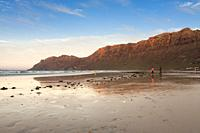 Sunset in the shore of a beach with persons walking along the shore of the sea. Famara, Lanzarote. Spain.