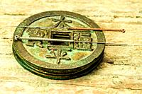 acupuncture needles on antique Chinese coin.