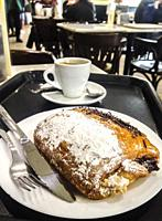 Having pain au chocolat or napolitana at Coffee Shop. Cake with plate, tray, coffee cup and cutlery. Selective focus.