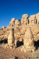 Statue heads, from right, Herekles & Apollo with headless seated statues in front of the stone pyramid 62 BC Royal Tomb of King Antiochus I Theos of C...