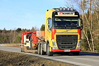 Salo, Finland - March 1, 2019: Yellow Volvo FH truck of Silvasti hauls Sandvik LH209L underground loader or LHD on trailer on highway on day of spring...