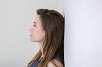 Side view of a young woman, with long hair, leaning against a wall.