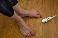 The feet of a young woman, with toenail polish, seen next to an electrical extension cord.