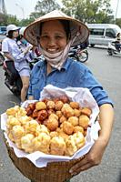 Woman selling pastries and deep fried vegetables from a wicker basket on the street, Hanoi, Vietnam, Asia.