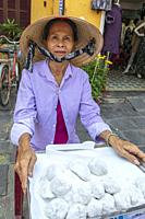 Local Vietnamese woman selling street kitchen meatballs wrapped in rice paper and dusted in coconut, Old town Hoi An, Quang Nam Provence, Vietnam, Asi...