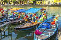 Traditional Vietnamese fishing boats decorated with silk lanterns with some used to ferry tourists along the river Son Thu Bon at Hoi An, Quang Nam Pr...