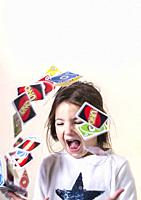Little girl playing with UNO cards. She is launching into the air the cards.