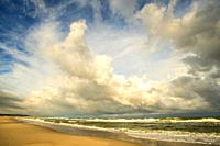 lonesome beach of the Baltic Sea with cloudy sky and surf.