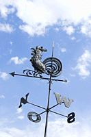 Rooster Weathervane Against Blue Sky and Clouds.