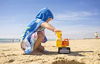 Baby boy playing on sand at the beach with excavator toy. He is wearing hooded poncho towel.