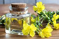 A bottle of evening primrose oil with fresh evening primrose flowers in the background.