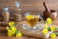 A cup of herbal tea with fresh mullein flowers on a rustic background.