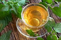 A cup of nettle tea with fresh plant on a rustic background.