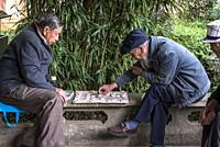 Locals playing Go - Chinese board game, Green Lake Park, or Cuihu Park, a local central located park, Kunming, Yunnan province, China.