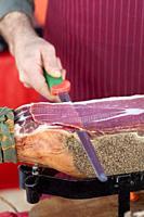 Italy, Umbria, Norcia, Stall Market, Market Stall Trader Carving a Ham. . . .