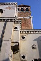 architectural contrast, brick church tower behind very different building with odd round windows set in squares and one wall sculpture showing, Venice...