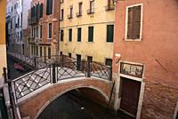 short bridge over narrow canal, yellow and rust-red buildings, muted colors, Venice, Italy.