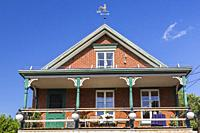 Second story balcony of an old 1900s red brick cottage style house with white and green trim plus decorated wooden posts, Quebec, Canada.