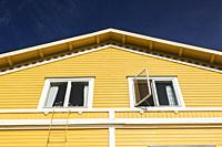 White windows on exterior side wall of a yellow two story house, Porvoo, Finland, Europe.