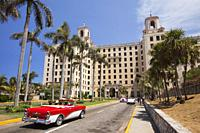 View to the Hotel Nacional in Vedado district with an old American car used as taxi in the foreground, Havana, La Habana, Cuba, West Indies, Central A...