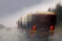 Driving along highway in rain and passing a semi truck with a load of machinery, rainwater splashing, blurred view.