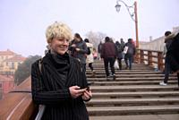 Stylish young woman in pin-stripe coat, wire-rim glasses, blond-white short hair, on Accademia bridge with little smile holding phone, foggy day, Veni...
