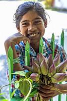 Myanmar (formerly Burma). Kayin State (Karen State). Hpa An. Saleswoman lotus flowers.