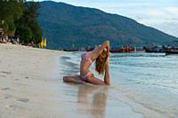 Girl practicing yoga in pigeon pose on the beach with Thai longtail boats, Ko Lipe island.