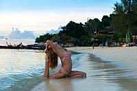 Girl practicing yoga in pigeon pose on the beach with Thai longtail boats, Ko Lipe, Thailand.