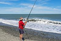 A man fishing from a beach in Greymouth, South Island, New Zealand.