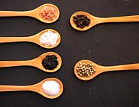 Wooden spoons with himalayan salt, black hawaii salt, common salt, salt flakes and peppercorns on a slate plate.