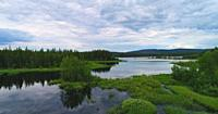 Clouds are reflected in the glassy water of a forest lake on a summer day in northern Sweden.