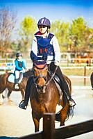 Girl rides her horse in the outdoor riding-little girl takes outdoor riding lesson.