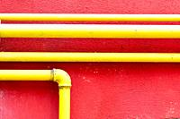 yellow gas pipe on a pompeian red wall.