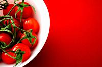 Cherry tomatoes in white bowl on red background