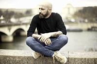 man sitting at riverbank, Seine river, in Paris, France