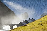 Elan Valley, Powys, Wales, UK. Visitors walk across a bridge as water cascades over the Caban-coch dam, at Elan Valley village near Rhayader in Powys,...