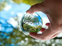 An unrecognizable person with a crystal ball in his hand with a landscape reflection.