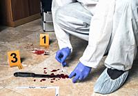 Expert Police takes blood sample from a blood knife at the scene of a crime, conceptual image.