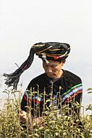Yiliang, China - March 24, 2019: Black Yi man dressed in a traditional attire picking up tea leaves in Baohong mountain, Yiliang in Yunnan.