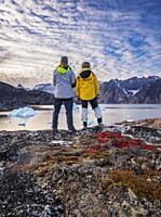 Tourist enjoying the view, Scoresbysund, Greenland.