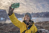 Woman taking a selfie with a cell phone, Scoresbysund, Greenland.