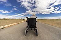 Old woman in wheelchair on the middle of a road