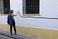 Young woman following a line painted on a wall with her finger. Cordoba, Andalusia, Spain.